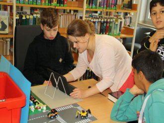 Eine Referentin zeigt drei Jugendlichen etwas auf dem Ipad