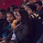Ein junges Mädchen hält ein Mikro in einem Kinosaal