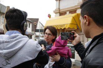 Jugendliche interviewen und filmen mit einem Smartphone eine Passantin