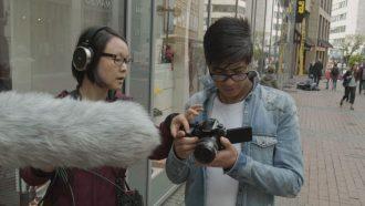 Ein Mädchen mit einem Außenmikro und ein Junge justiert eine Fotokamera