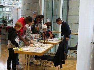 Schüler beobachten eine Aktion am Tisch